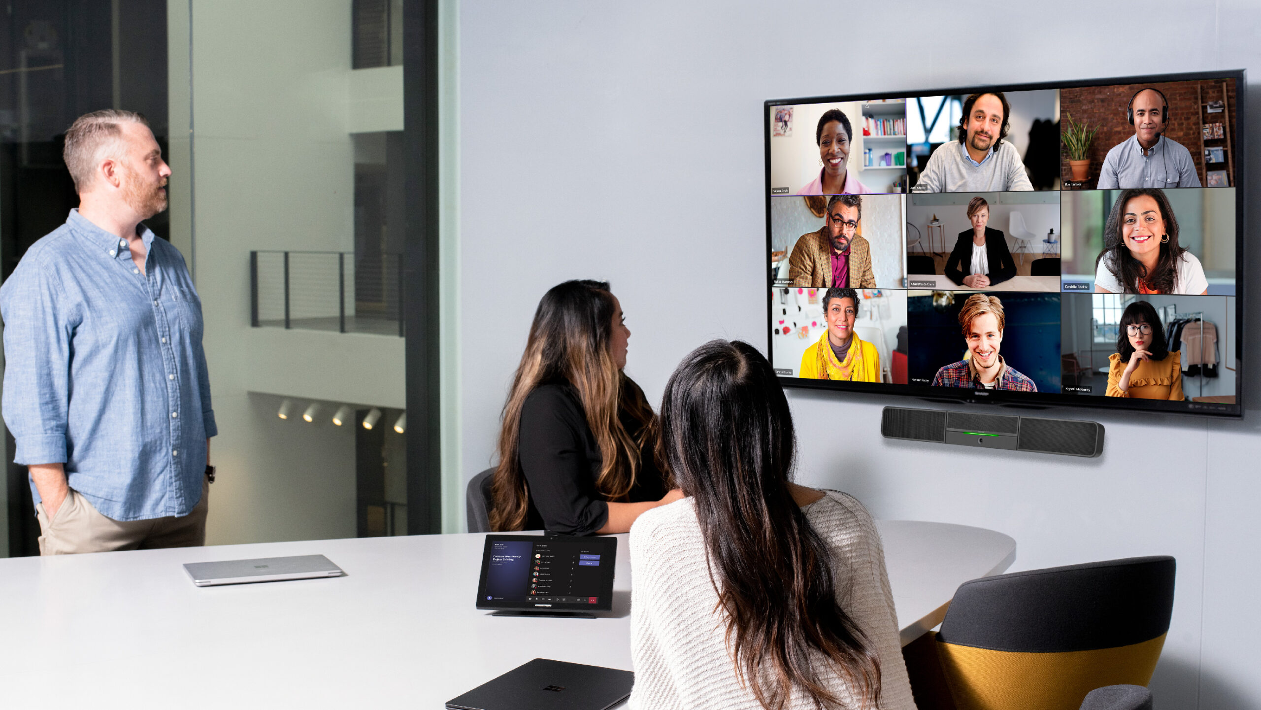 One male and two females in medium conference room with a Crestron Microsoft Teams Rooms on Android device and touch display being used for remote video meeting with Teams Meetings. Large mounted display showing remote participants and two Surface Device
