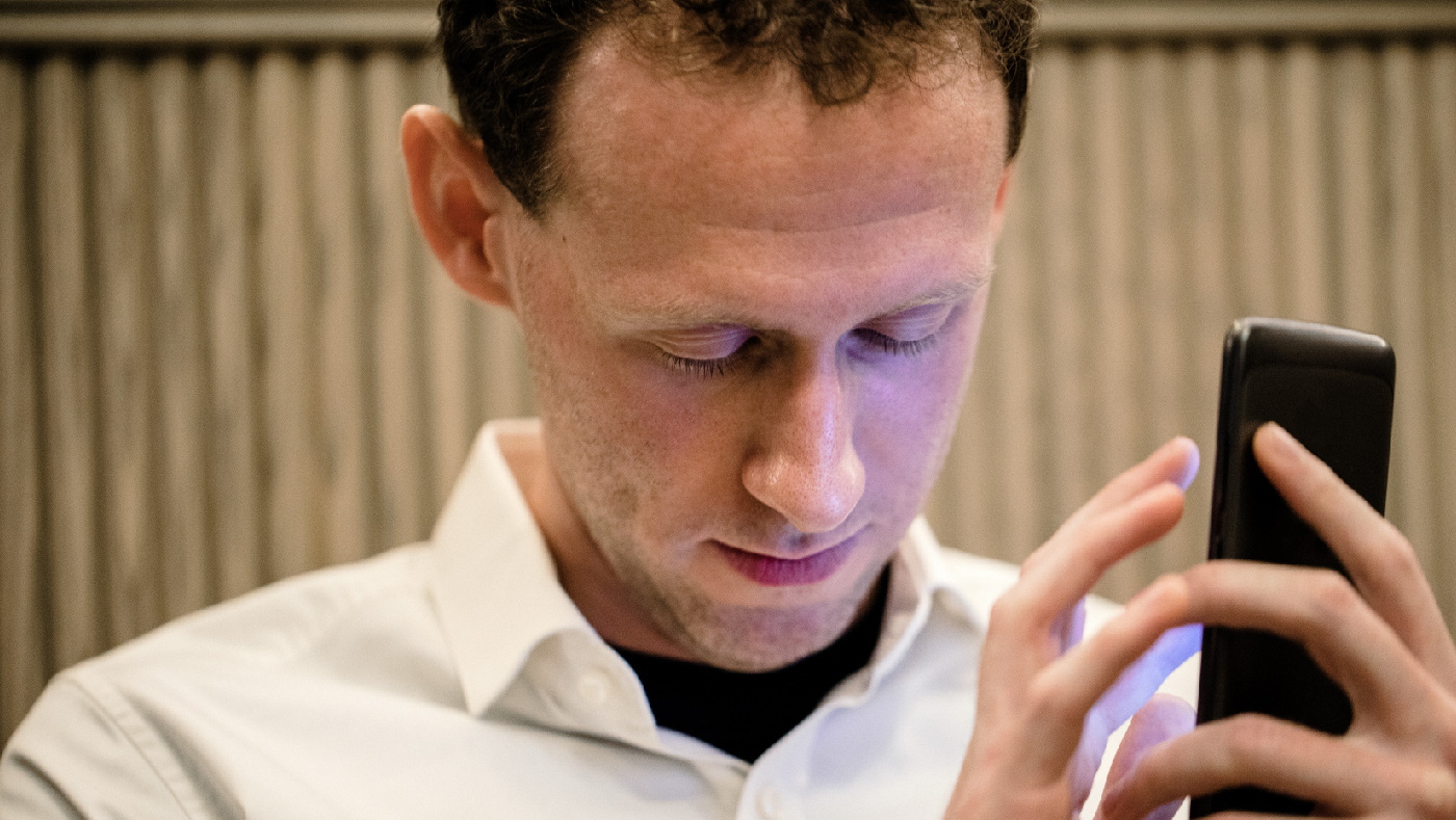 A close-up of a man wearing casual clothing, he has his smartphone in his hand and he is using an assistive mobile app for people with vision disabilities to assist him.