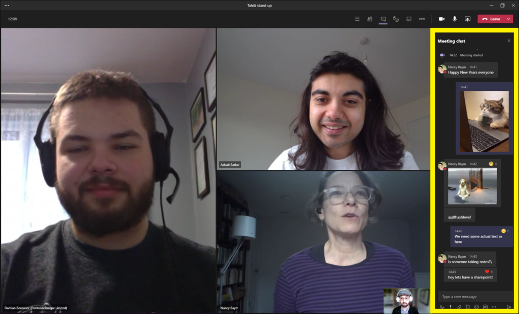 """Three people meet in Microsoft Teams. On the left, a person with a beard is wearing headphones with a microphone and is smiling. They wear a black t-shirt, and they are standing in front of a curtained window in a house. A wall to his left has a gallery of pictures. Moving clockwise, another person has long, dark hair and is also smiling. They wear a white t-shirt. They are standing in a room with white walls, and a turned-off lightbulb hangs above their head. Next, a person is talking. They have glasses, a purple shirt on with horizontal stripes, and stand in a room with a bookshelf and floor lamp to their right. There is also another person in a small window at the bottom of the screen, wearing a hat, cardigan, and headphones. The sidebar chat is outlined with a yellow border. From top to bottom, the chat window reads: Meeting Chat. Nancy Baym: """"Happy New Years everyone."""" A picture of a cat with glasses working at a laptop. Nancy Baym: A video of a dog levitating next to a tree. This video has a """"laugh"""" reaction. A string of unintelligible text in the chat follows. """"We need some actual text in here."""" Nancy Baym: """"Is someone taking notes? Hey let's have a sharepoint!"""" A heart reaction shows on the last comment."""