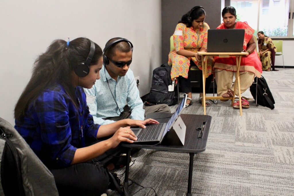 A woman and man both wearing headphones connected to a laptop on a small table in front of them are seated on a carpeted floor. The woman has her hands on the keyboard. Behind them, two women, one wearing headphones, are seated at a folding table, their attention on a laptop in front of them. A backpack and messenger bag rest on the floor beside them.