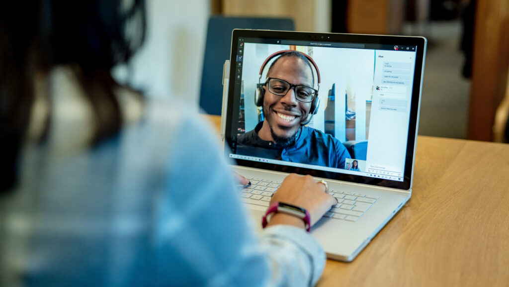 Woman at a desk using a Surface laptop to make a Microsoft Teams video call with one man smiling and wearing a headset. Business Voice conference call/meeting device is in the background.