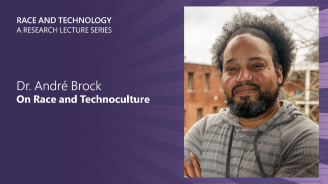 """Dr. André Brock posing for the camera, introducing his lecture """"On Race and Technoculture"""""""