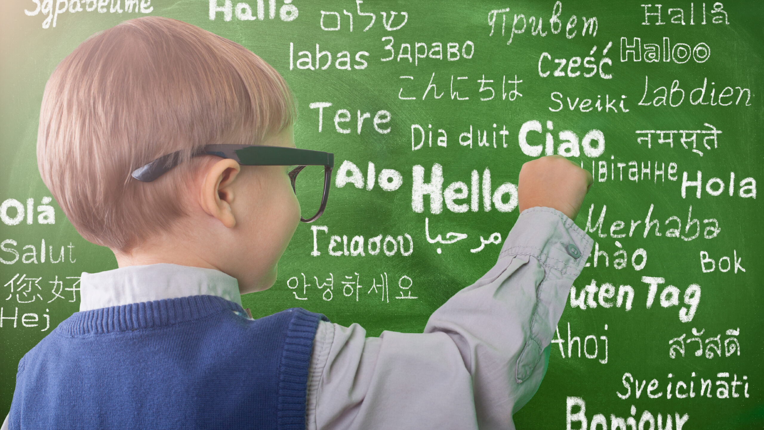 """Photo of a young child writing on a chalkboard. The word """"hello"""" is written on the chalkboard in multiple languages."""