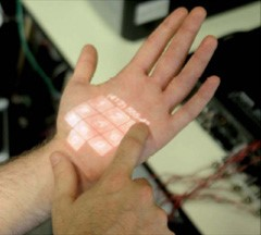 A sensing armband and a pico projector enable interactive elements to be rendered onto a person's skin.