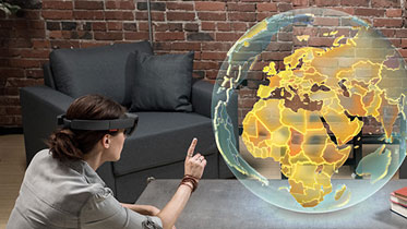 Woman interacting with virtual globe using Holo Lens