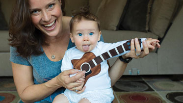 A woman and baby plan a ukelele to a relative using Skype.