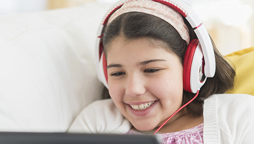 young girl using a laptop with headphones