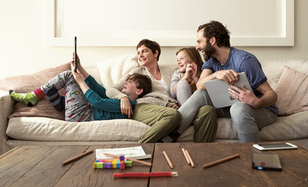A family sits on a couch holding smart devices and laughing.