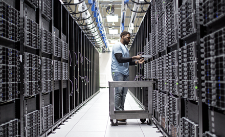 A man at work in an aisle of a datacenter.