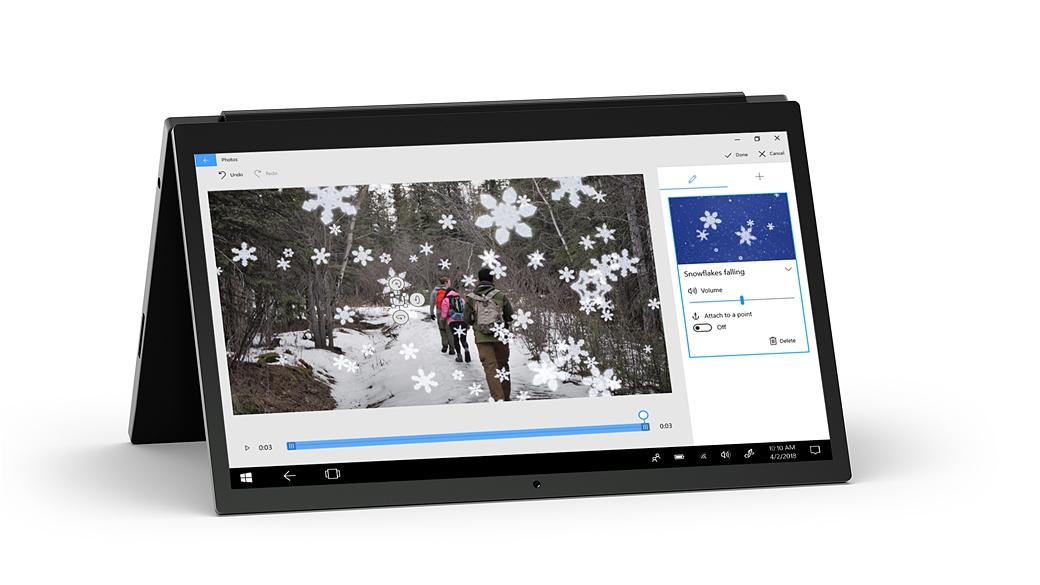 Equipo portátil con la tapa hacia atrás y mostrando la aplicación Fotos con una imagen de mochileros que andan por un bosque, superpuesta con un efecto de copos de nieve en 3D.