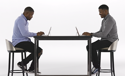 Image of twins sitting at a table, each with a laptop open.