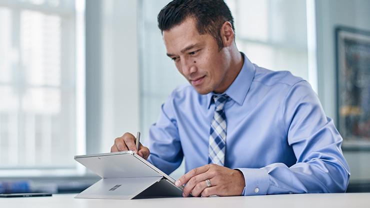 Hombre que escribe sobre Surface Book