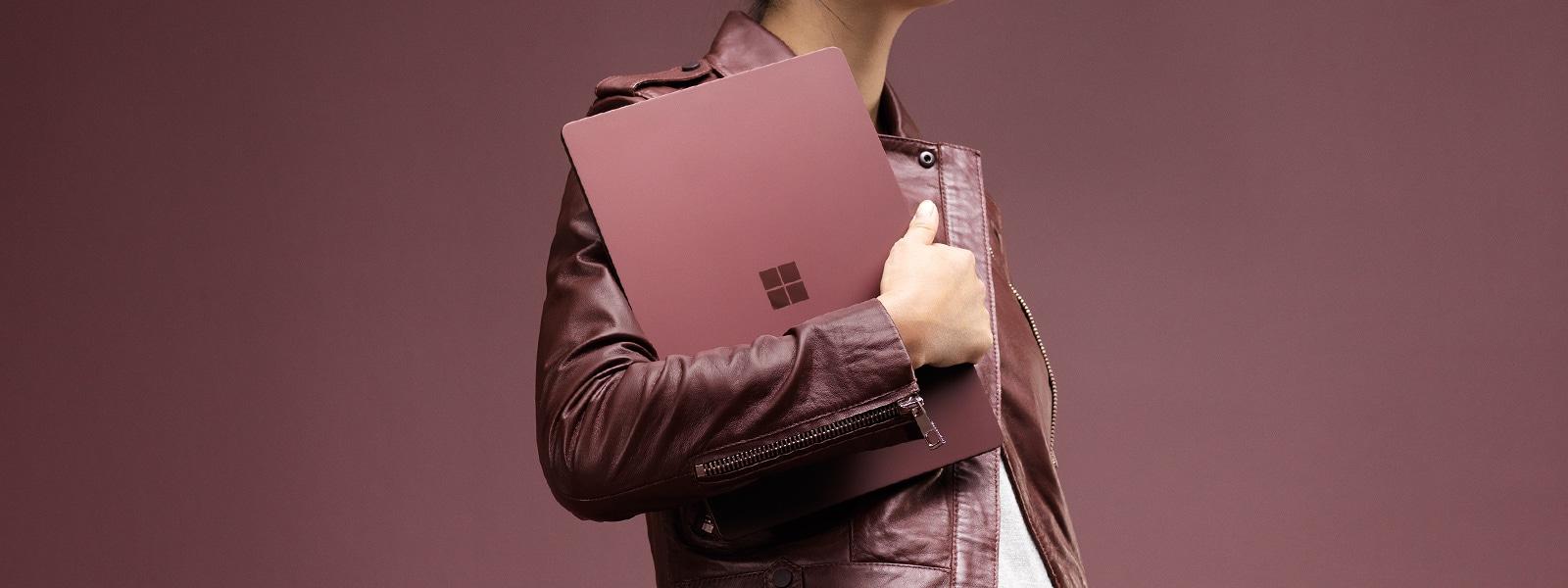 Mujer elegante sosteniendo un dispositivo Surface Laptop de color burdeos cerca del pecho