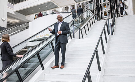 Image of a financial services worker walking down a flight of stairs while checking his phone.