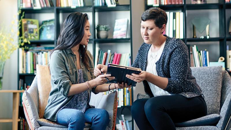 Dos mujeres que comparten una tableta