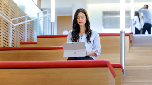 A woman sitting on the stairs, using a laptop