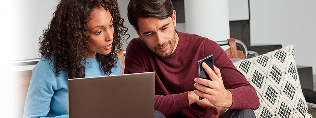A man and a woman with a laptop and a smartphone