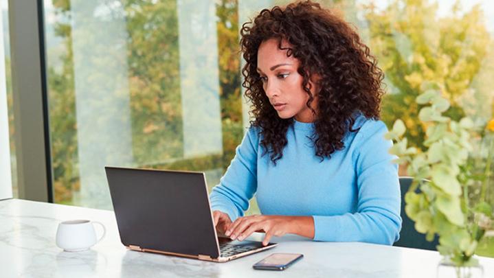 Una mujer sentada en un escritorio, utilizando una computadora