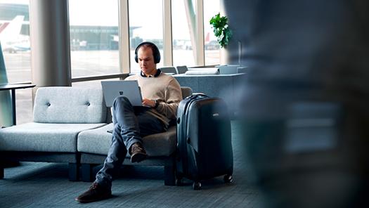 Fotografía de un hombre sentado con auriculares y un ordenador portátil