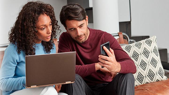 Un hombre y una mujer mirando una laptop y un teléfono
