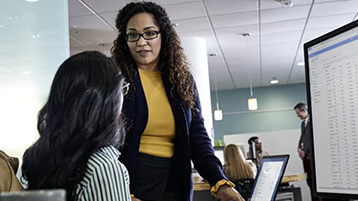 dos mujeres conversando frente a una computadora