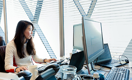 Image of an office worker looking at her computer monitors.
