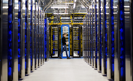 Image of a man walking through a datacenter.
