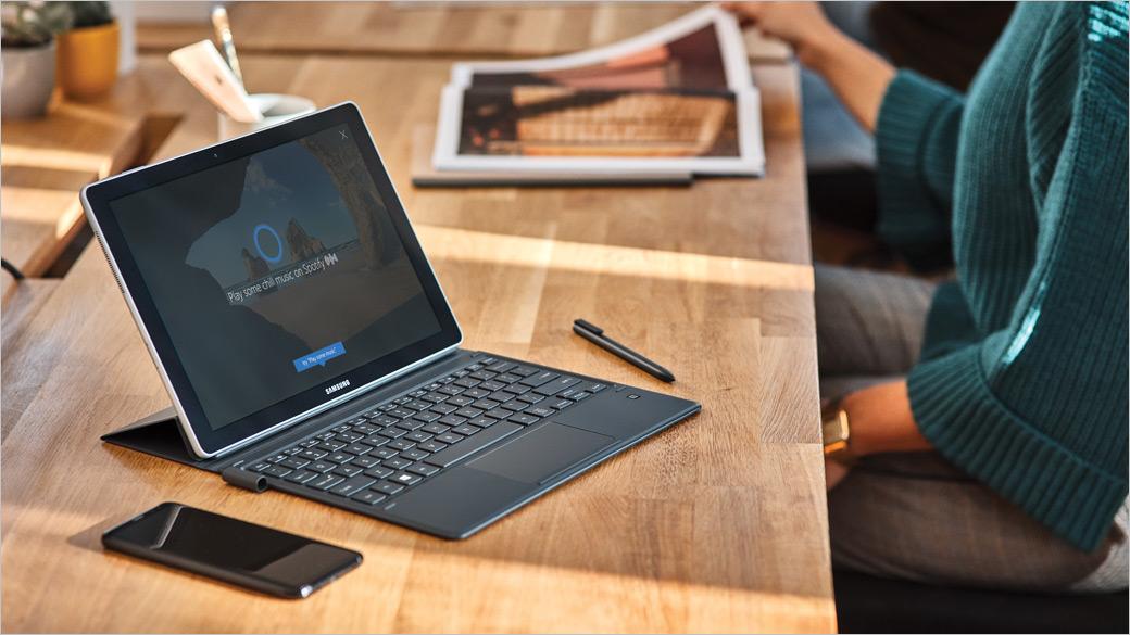 Une femme utilisant un ordinateur portable demandant à Cortana de jouer de la musique sur Spotify