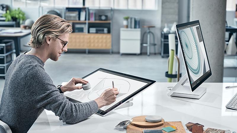 Homme dessinant sur l'écran d'un Surface Studio en utilisant le Dial dans un bureau moderne avec un autre Surface Studio en face de lui.