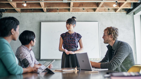 Une femme donne une présentation dans une salle de conférence.