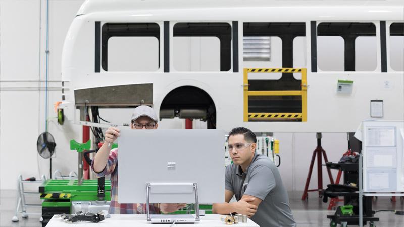 Deux personnes regardent l'écran d'un Surface Studio dans un laboratoire de fabrication.