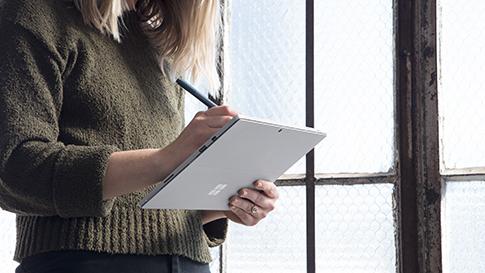 Femme utilisant une Surface Pro en mode bloc-notes.
