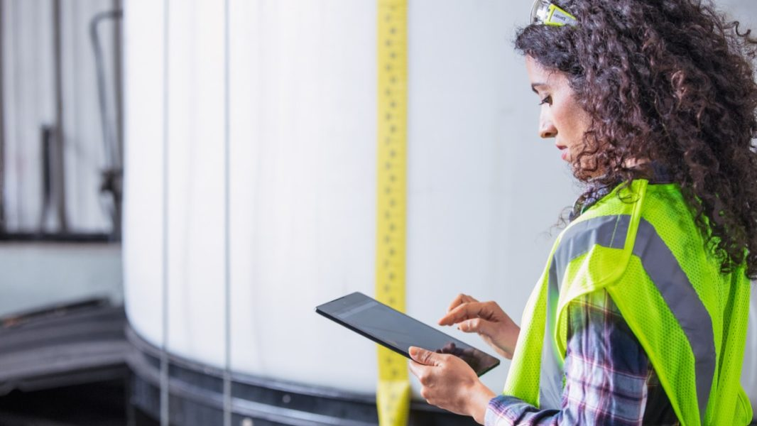 Female worker wearing neon vest and safety glasses using tablet. Industrial vats visible in background.