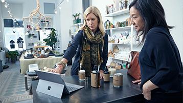 Deux femmes en entreprise interagissant avec Surface Pro.