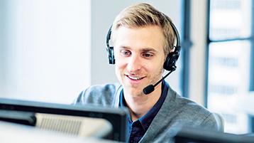 Professionnel du support technique au téléphone, portant un casque, face à un ordinateur.