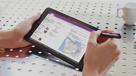 Les mains d'une femme tiennent un stylo et une tablette dont l'écran affiche un onglet OneNote montrant une carte et un texte. Les mains reposent sur une table métallique perforée et brillante, à côté d'une tasse à café blanche à moitié pleine et d'une so