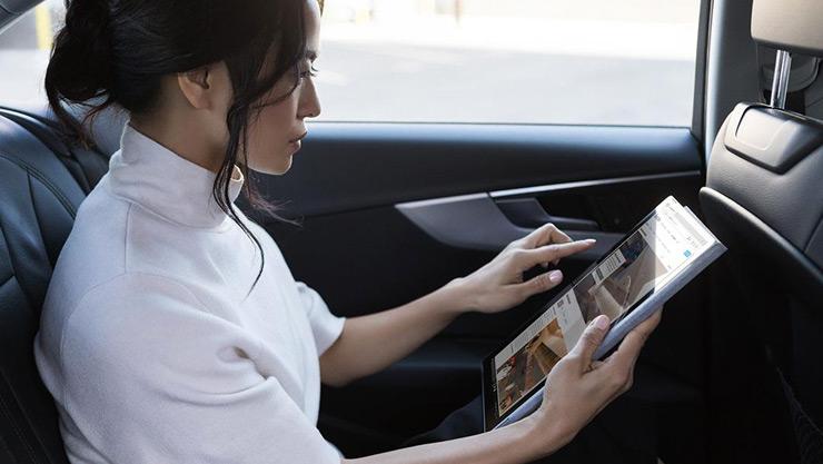 Femme assise dans sa voiture qui utilise son appareil Surface en mode tablette en déplacement