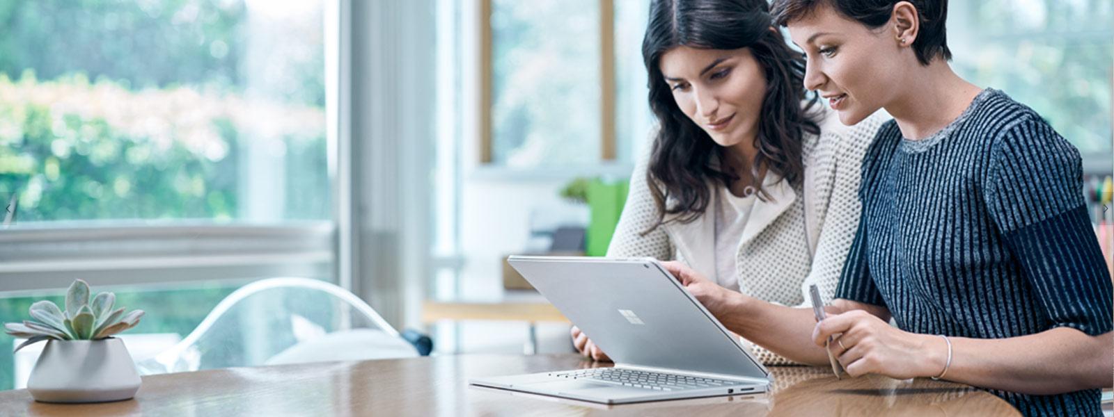 Une femme utilisant Surface Studio zoomant par un mouvement de pincement avec le stylet et l'interface tactile.