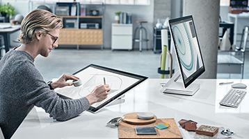 Homme dessinant sur l'écran Surface Studio en utilisant le Surface Dial dans un bureau moderne avec un autre Surface Studio en face de lui