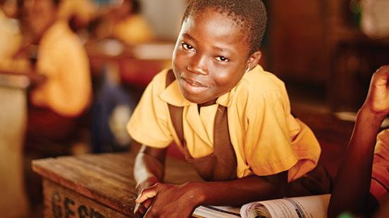 Jeune garçon souriant dans une salle de classe