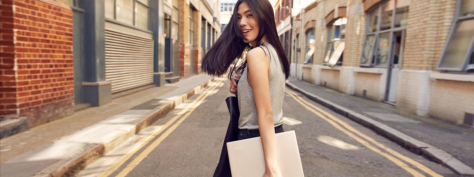 Femme marchant dans la rue avec le Lenovo YOGA910
