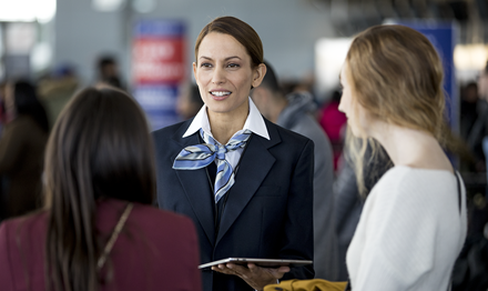 A concierge helps customers at an airport with a device.