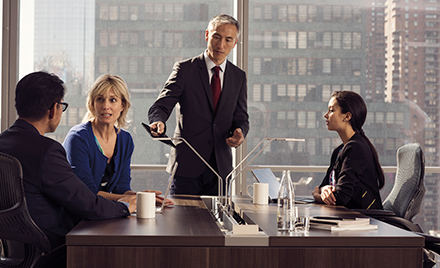 Image of a meeting, wherein four colleagues gather around a desk to discuss a project.