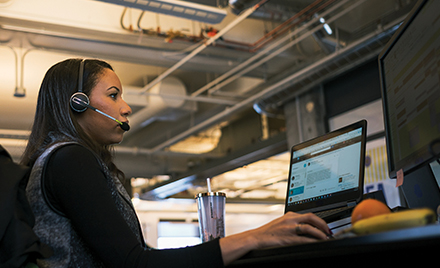 Image of a firstline worker working at her desk, answering a call on her headset.