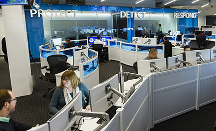 "Image of a modern workplace. Above two workers speaking with one another are the words ""Protect,"" ""Detect,"" and ""Respond."""