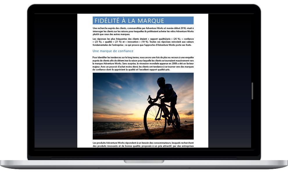 Image montrant un ordinateur portable déplié sur lequel un utilisateur travaille sur un document Word.