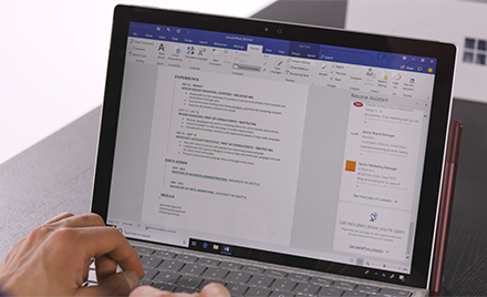 Image of a person typing on a laptop, a Word document open.