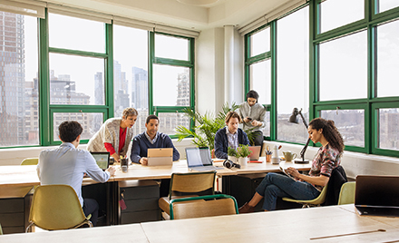 Image for: Image of a group of coworkers collaborating in a conference room, each on a variety of different devices.