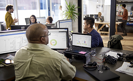 Image for: Image of an office of tech workers using Microsoft Office products.