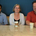 Nampoothiri, Bregler, and Reutter sit together at a table smiling at the camera in a Microsoft building.